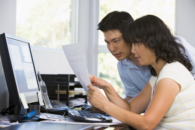 Couple in home office with computer and paperwork pointing